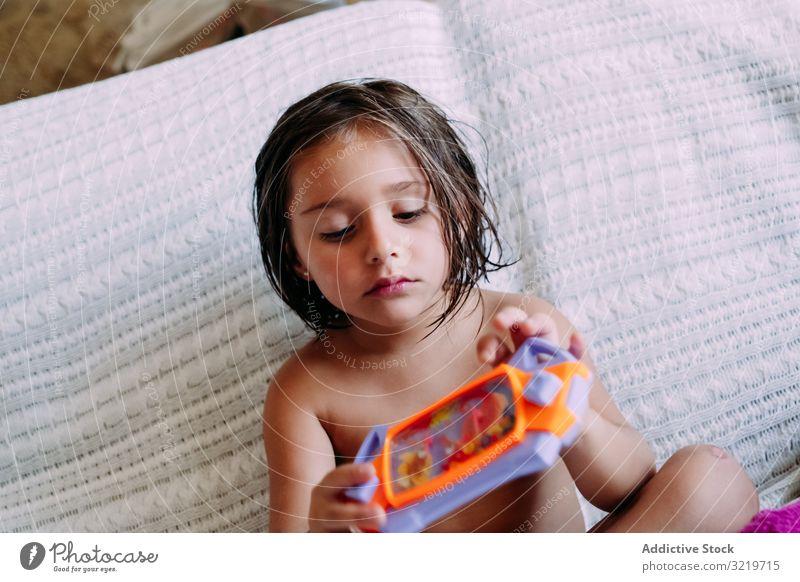 Kind auf der Couch sitzend Sofa heimwärts Spaß Kindheit Lifestyle Liege Sitzen Raum niedlich wenig modern klein Barfuß lässig genießend lieblich Zeitgenosse
