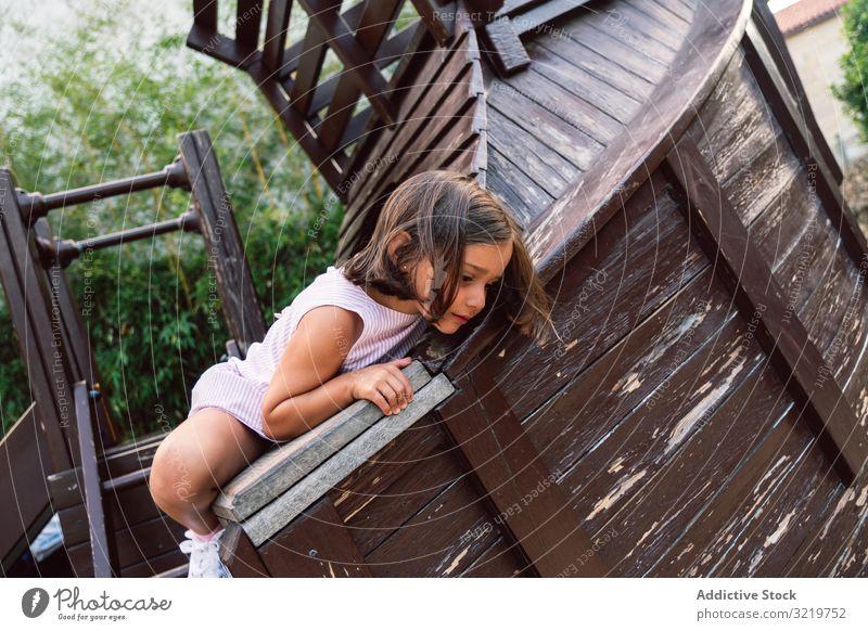 Lächelndes Mädchen klettert auf Holzspielplatz Kind spielen Aufstieg Spaß Spielplatz Aktivität Sport Glück wenig Entertainment Park Mut Lifestyle spielerisch