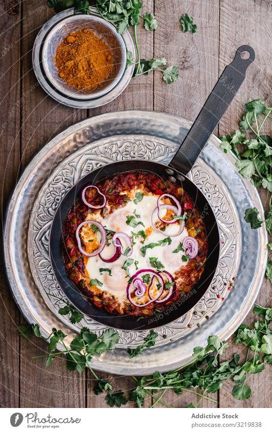 Duftende Shakshuka mit Zwiebelringen in der Pfanne Küche traditionell shakshuka Kurkuma Lebensmittel grün Mahlzeit Gemüse Schalen & Schüsseln Rezept Tisch