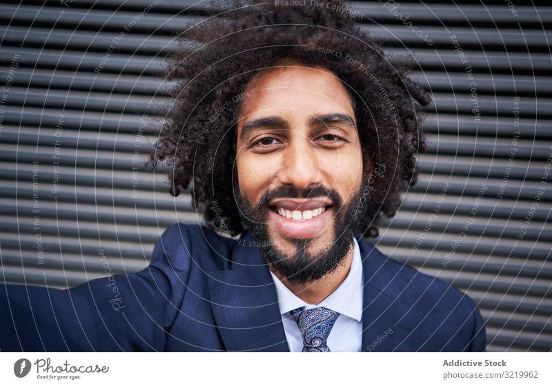 Fröhlicher ethnischer Mann, der Egoismus nimmt und lächelt modern Geschäftsmann formal Afrikanisch schwarz Smartphone Selfie Wand Lächeln Glück Afro-Look heiter