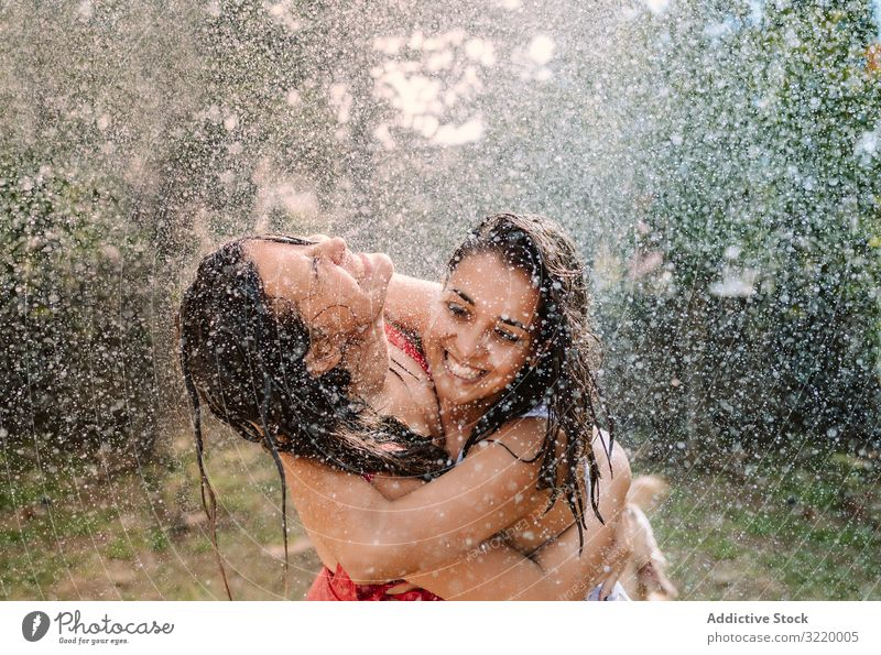 Freunde in Badeanzügen umarmen sich unter Wassertropfen Frauen platschen Garten Tropfen Freundin Umarmung Feiertag fallen Sommer Badeanzug Schlauch Spaß heiter