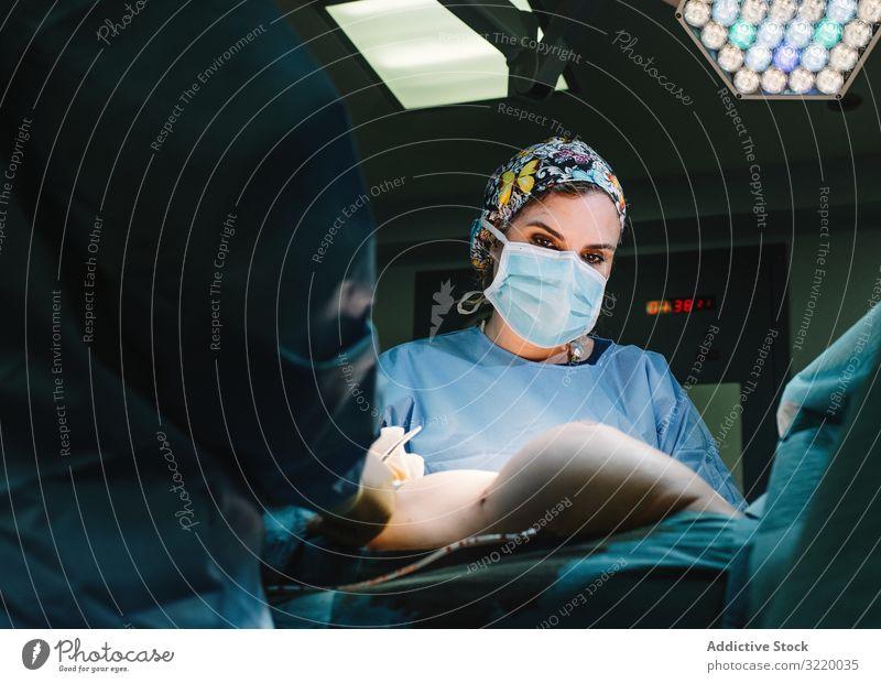 Konzentrierte Chirurgin bei der Arbeit Frau Arzt Chirurgie Krankenhaus Operation Medizin Beruf Konzentration jung ernst achtsam chirurgisch Kleid blau