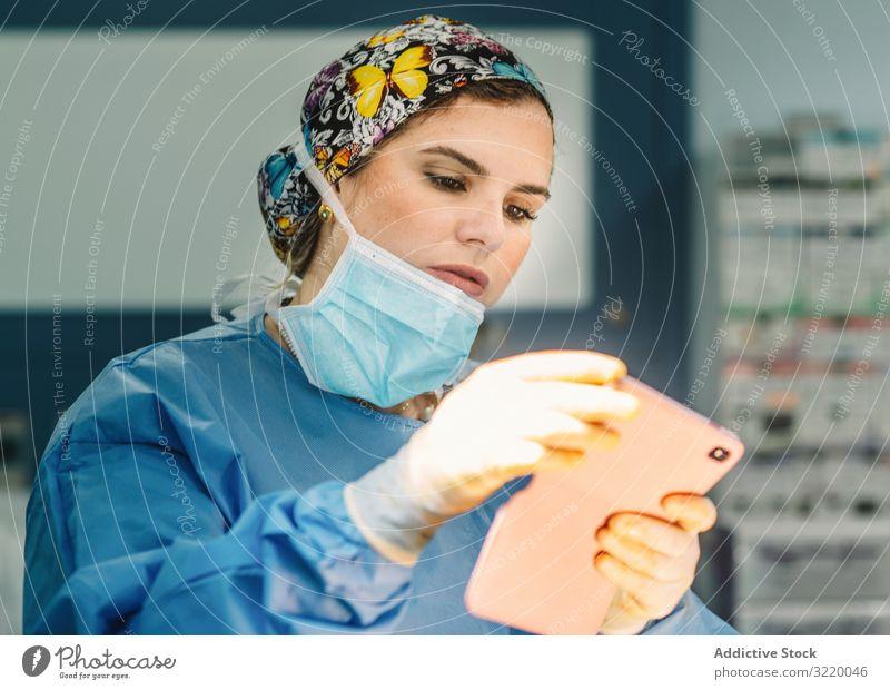 Ärztin stehend mit Smartphone Chirurg fotografierend Frau Arzt Medizin Krankenhaus benutzend Operation Chirurgie Klinik jung ernst schön attraktiv konzentriert