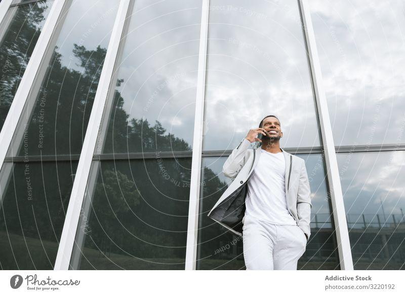 Eleganter schwarzer Mann spricht Smartphone schiefes Gebäude sprechend Business Architektur Anzug professionell ethnisch Außenseite Afrikanisch Surfen