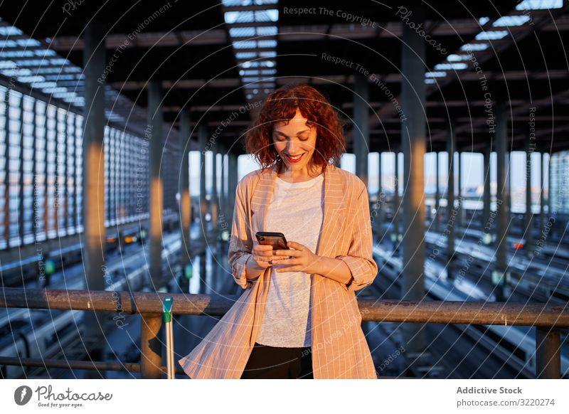 Lächelnde junge Frau beim Telefonieren am Bahnhof Eisenbahn Smartphone Anruf reisen Station Business Urlaub Tourist Mitteilung Terminal Abheben Koffer Abend