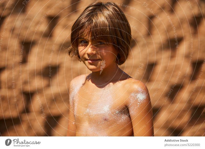 Junge mit Sonnencreme auf dem Körper, der in die Kamera schaut Kind Sahne Sommer Strand Schutz Urlaub Pflege Hilfsbereitschaft Kindheit Familie bewerben Bräune