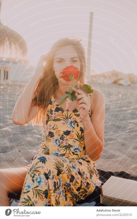 Frau sitzt am Strand und schnüffelt an Rose und schaut in die Kamera Roséwein romantisch nachdenklich besinnlich sonnig Liebe Glück Sommer träumen Sand Blume