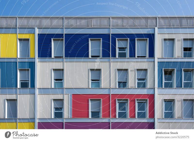 Fassade eines modernen mehrfarbigen Gebäudes mit schmalen Fenstern Außenseite farbenfroh Architektur Haus Anwesen Konstruktion Investition wohnbedingt Struktur
