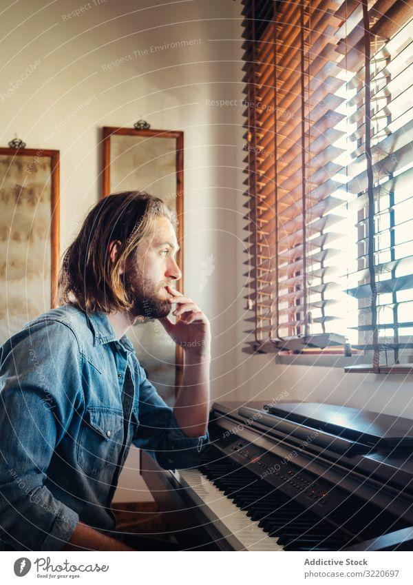 Nachdenklicher Mann spielt zu Hause Synthesizer komponieren Klavier Melodie nachdenklich besinnlich brutal spielen heimwärts gutaussehend kreativ Inspiration