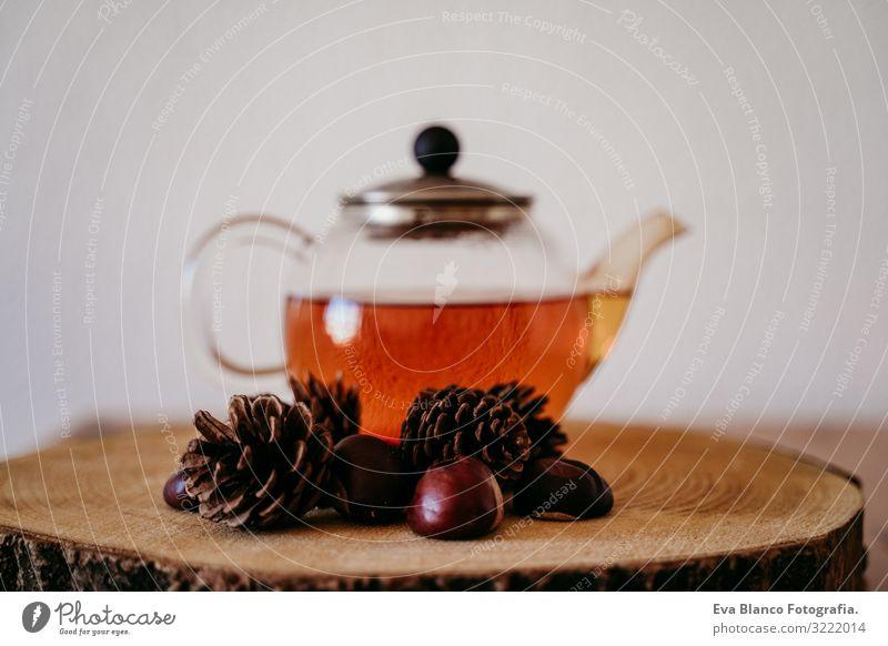 Teekanne mit Tee auf einem Holztisch. Daneben Ananas und Kastanien. Morgens, tagsüber. Herbst-Saison braun Innenaufnahme Menschenleer heimwärts Haus Tag