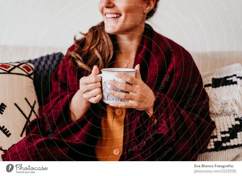 Schöne Frau auf dem Sofa sitzend, eine Tasse Tee genießend. Lebensstil im Haus, Herbstsaison Kaffee heimwärts Morgen Kaukasier Lifestyle Innenaufnahme Frühstück