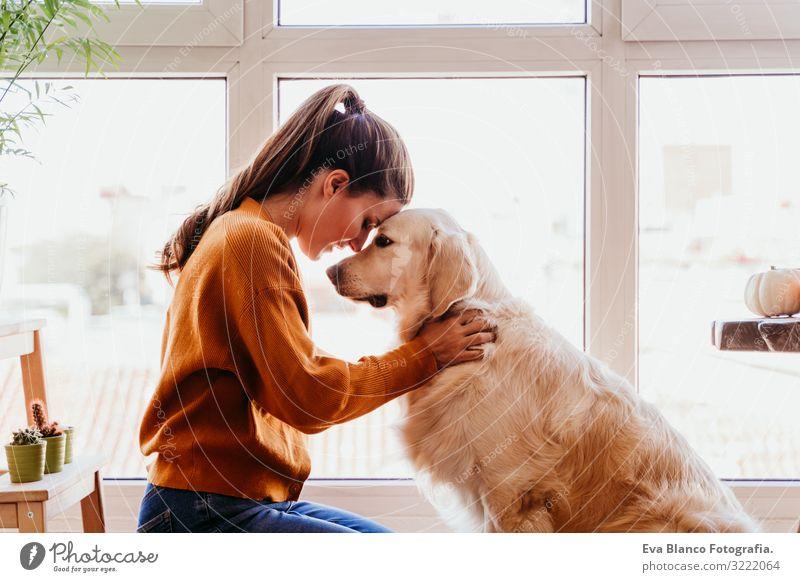 Schöne Frau, die zu Hause ihren bezaubernden Golden Retriever Hund umarmt. Konzept der Liebe zu Tieren. heimwärts Umarmen Lifestyle Innenaufnahme Zusammensein