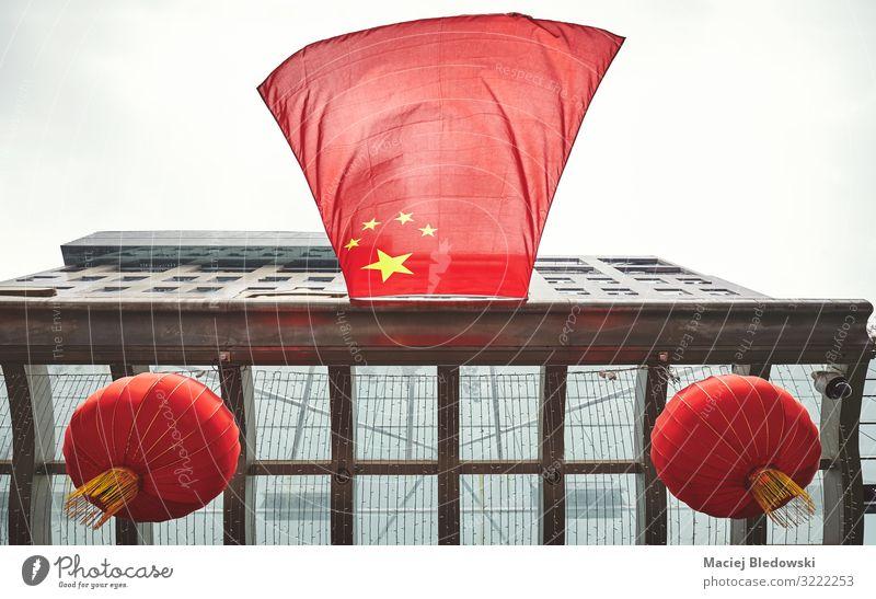 Blick auf die chinesische Flagge und rote Laternen an einem Gebäude. Himmel Wind Stadt Dach Fahne fliegen Symmetrie Zukunft Chinesisch Symbole & Metaphern China