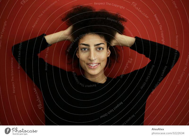 Portrait einer jungen Frau vor roter Wand Stil Freude schön Wellness Leben Wohnung Junge Frau Jugendliche 18-30 Jahre Erwachsene Pullover schwarzhaarig