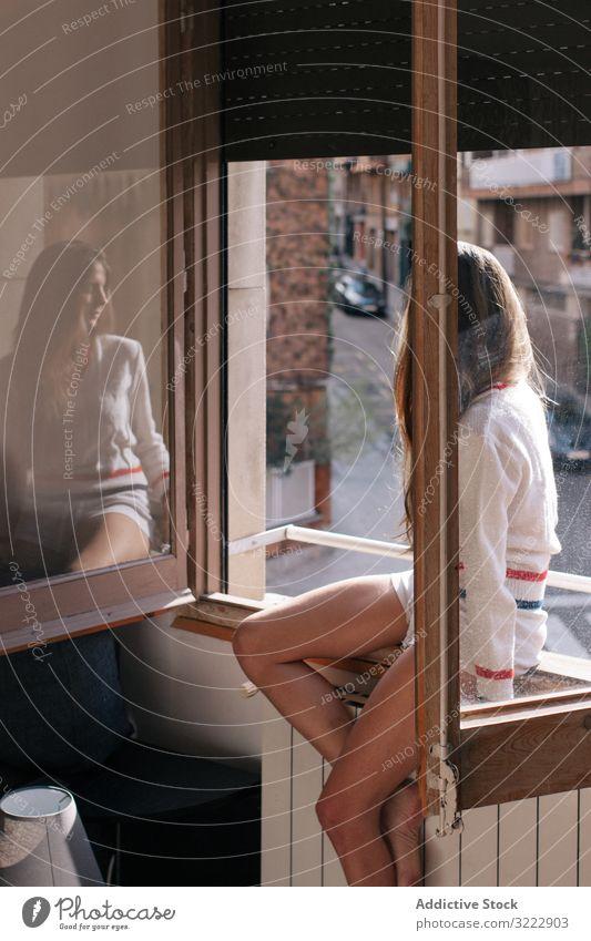 Frau sitzt auf der Fensterbank besinnlich Angebot nachdenklich heimwärts Fensterbrett Windstille attraktiv Appartement lässig jung schön hübsch Sitzen verärgert