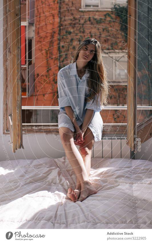 Frau sitzt auf der Fensterbank besinnlich Bett Angebot Schlafzimmer nachdenklich heimwärts Fensterbrett Windstille attraktiv Appartement lässig jung schön