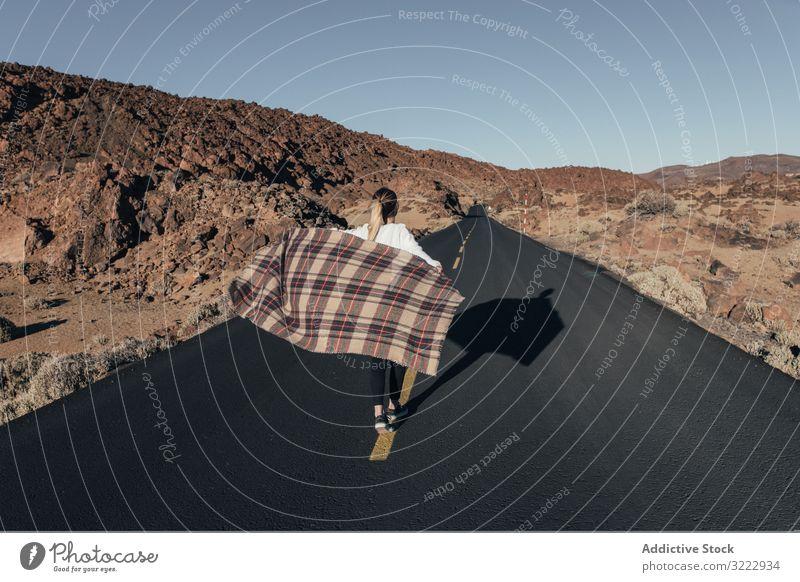 Frau mit Plaid geht auf leerer Straße Freiheit Teneriffa Träumer sorgenfrei winkend laufen Reisender Ausflug Decke Spaziergang Wind wüst Berge u. Gebirge Hügel