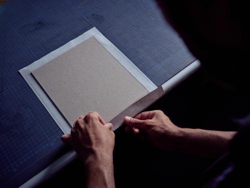 Buchbinder, der Stoff auf den Einband für ein Buch legt Buchmacherei Deckung Kunst Gewebe Typographie messen Bucheinband Beteiligung Page Zusammenbau Handwerk