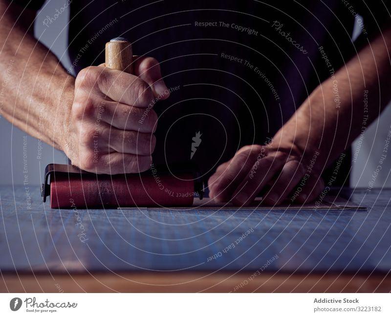 Buchbinder mit Vintage-Handroller Mann Buchbinderei Handwerk Rolle manuell Werkzeug Buchmacherei anstrengen Karton Presse Arbeit Arbeiter Beruf männlich Person