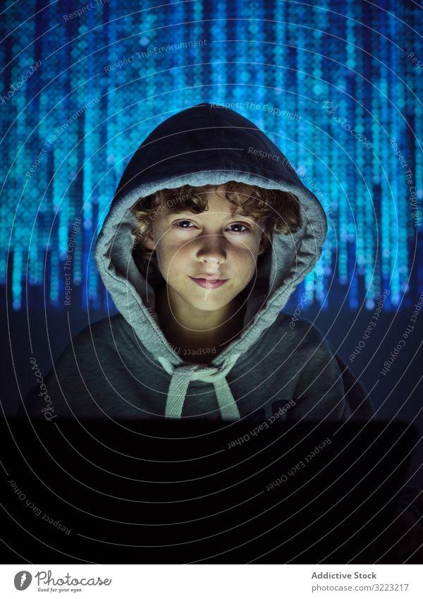Kleiner Hacker schaut in die Kamera Laptop Code Junge Datenbank wenig benutzend Computer Programmierer Virus digital Kennwort Software Kind Gerät Apparatur