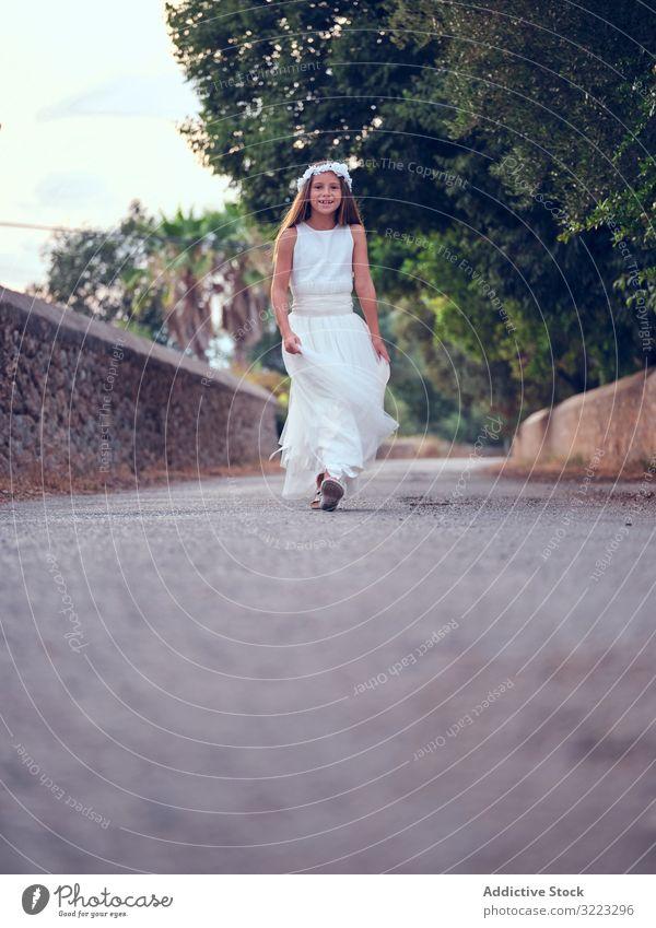 Bezauberndes kleines Mädchen in luftigem Kleid geht im Park spazieren laufen Kind rennen Freizeit Genuss Glück süß wenig bezaubernd Frau niedlich schön Unschuld