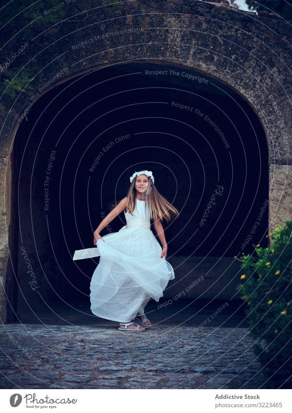 Hübsches kleines Mädchen in luftigem Kleid tanzt unterm Bogen Tanzen Kind Freizeit genießend Glück wenig bezaubernd Frau niedlich schön Unschuld Reinheit