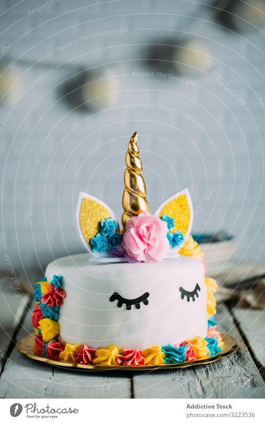 Niedliche Einhorntorte mit gemalten geschlossenen Augen Kuchen süß geschmackvoll Geburtstag hell Tisch appetitlich Feiertag Dekoration & Verzierung