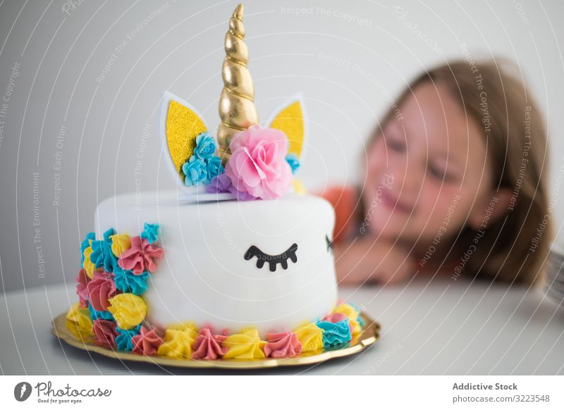 Heller Einhorn-Kuchen für zufriedenes Mädchen bei Tisch Party Kindheit hell Glück wenig Feiertag Geburtstag Dekoration & Verzierung zu feiern heiter Spaß