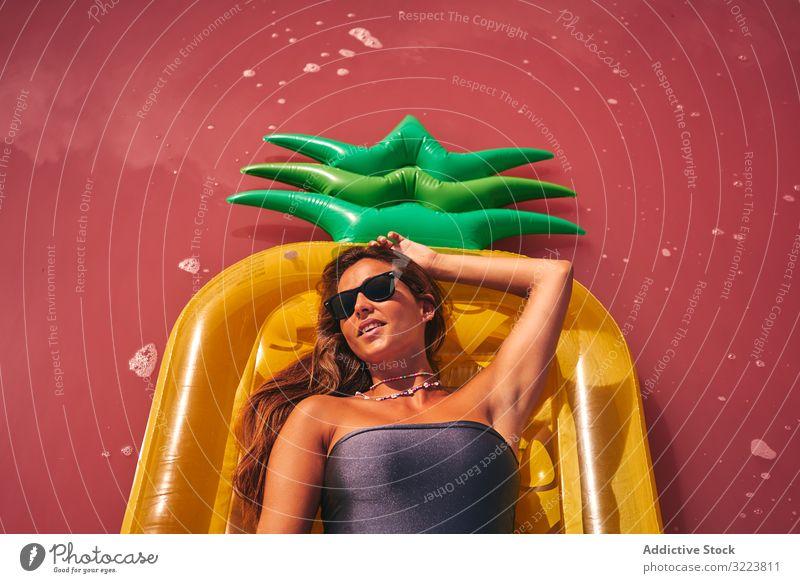 Verträumte Frau ruht auf aufblasbarer Matratze Kälte Lügen Sommer Luftmatratze verträumt rosa Reichtum einladend ruhen Sonnenbrille Badebekleidung Rote Lagune