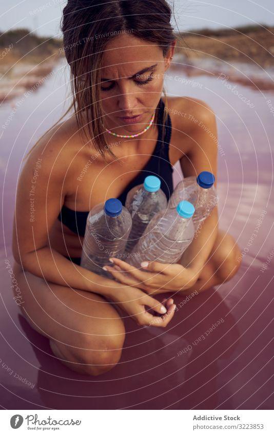 Besorgtes Weibchen im Badeanzug beim Müllsammeln im natürlichen See Verschmutzung Wasser Verunreinigung Frau abholen betroffen Pool pflücken Flasche Kunststoff