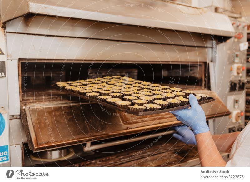 Nicht erkennbarer Konditor, der Gebäck in den Ofen schiebt Bäckerei Fall backen Dessert professionell Arbeit Koch Küchenchef Tablett Patisserie Vorbereitung