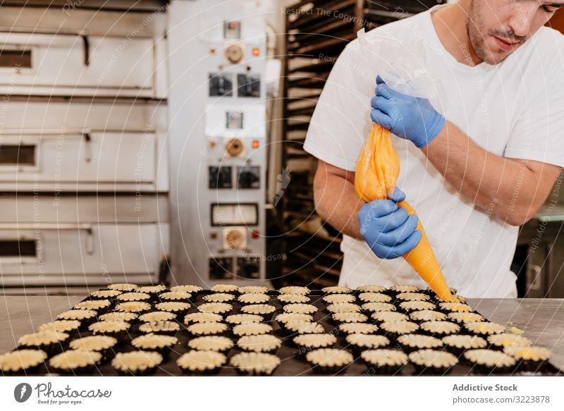 Getreidebäcker, der Gebäckbehälter mit Gelee füllt Konditor Bäckerei Götterspeise drücken Torte Tasche Fall Küche süß Lebensmittel Dessert kulinarisch