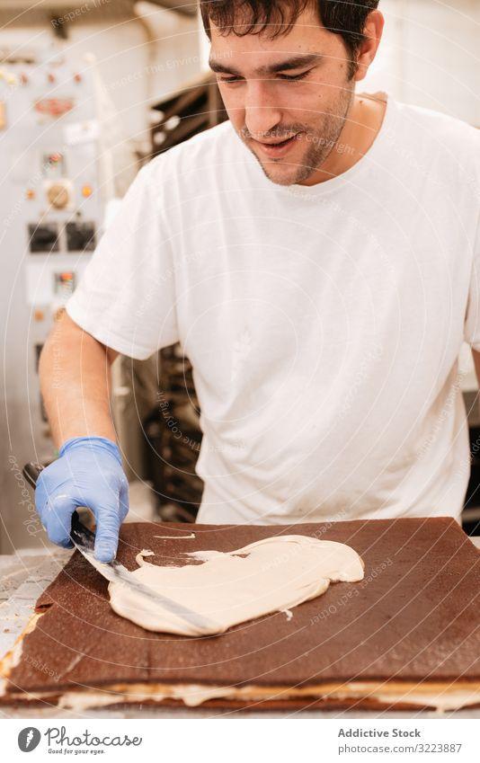 Anonymer Konditor dekoriert süßen Kuchen Dekor Bäckerei Sahne Küche Arbeit Koch Gebäck Lebensmittel lecker geschmackvoll Glasur Küchenchef Dessert Mann Uniform