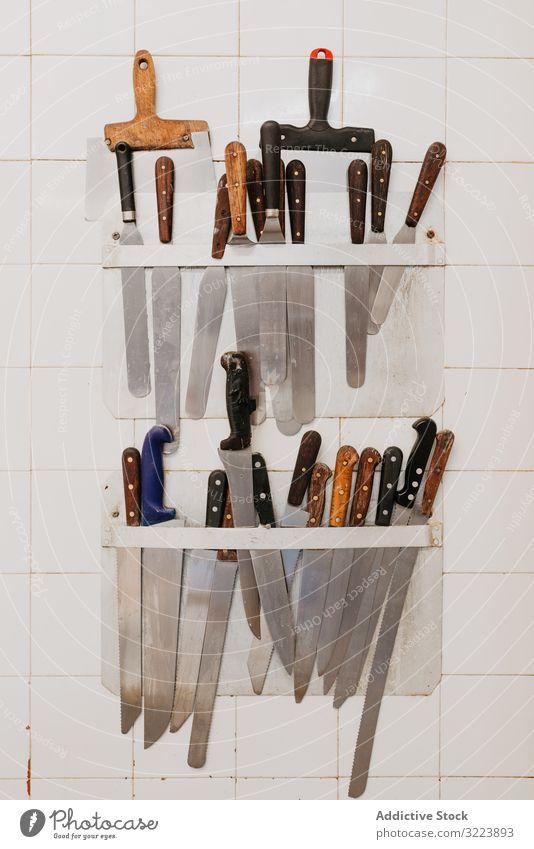 Kochwerkzeuge an der Wand hängend Werkzeug Küche Bäckerei Klammer Kulisse Messer Spachtel professionell Sammlung beigefügt gekachelt Vorbereitung Gerät