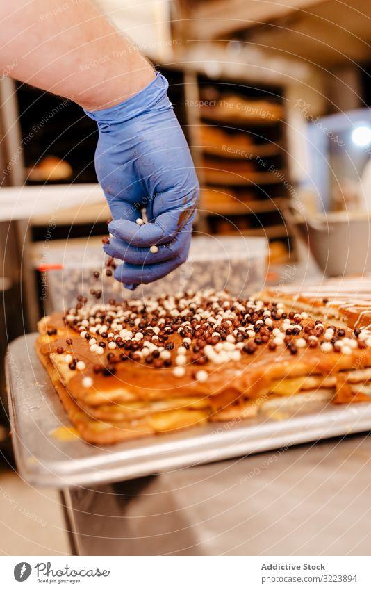Anonymer Bäcker streut Streusel auf Gebäck Konditor Bäckerei Aufstrich Dekor Tisch Qualität Kuchen Vorbereitung Kleinunternehmen frisch Beruf traditionell