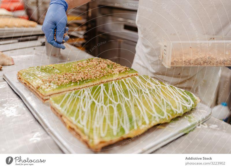 Bäcker verschüttet Krümel auf Kuchen Konditor Bäckerei verschütten Dekor Tisch Küche Gebäck Vorbereitung Kleinunternehmen Arbeit Job frisch Lebensmittel