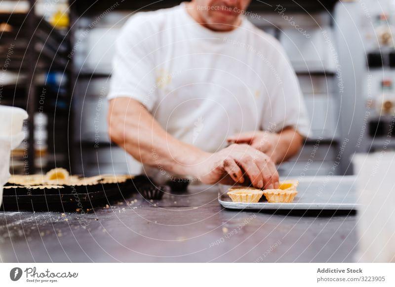 Getreide-Konditor, der kleine Kuchen dekoriert Bäckerei Sahne drücken Schokolade Tablett Koch Gebäck Lebensmittel frisch Qualität Vorbereitung Arbeit