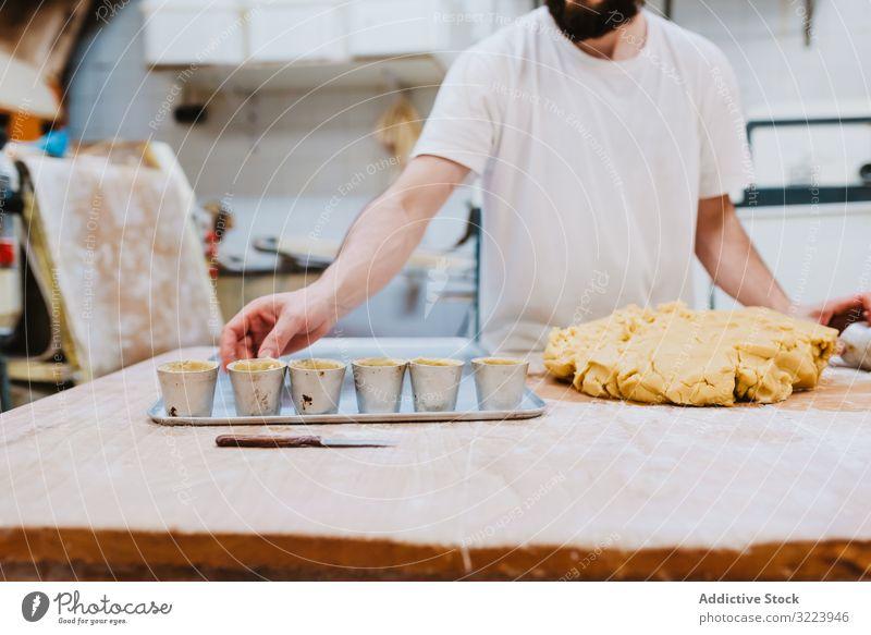 Bärtiger Konditor legt Teig in Tasse Bäckerei Teigwaren setzen Tisch Küche Gebäck Vorbereitung frisch Mann roh professionell Lebensmittel Küchenchef Restaurant