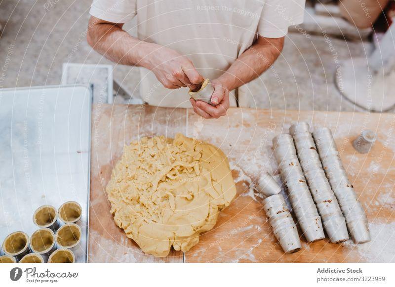 Nicht erkennbarer Koch legt Teig in Tasse Konditor Bäckerei Teigwaren setzen Tisch Küche Gebäck Vorbereitung frisch Mann roh professionell backen Lebensmittel