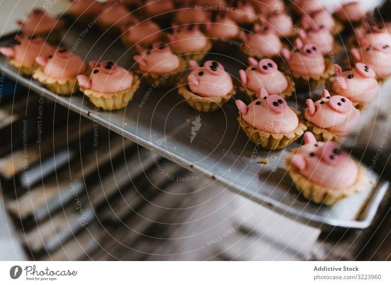 Tablett mit schweineförmigen Desserts in der Bäckerei Gebäck Schwein Ablage Form Symbol klein rosa Kuchen Ohr Schnauze Lebensmittel süß frisch backen