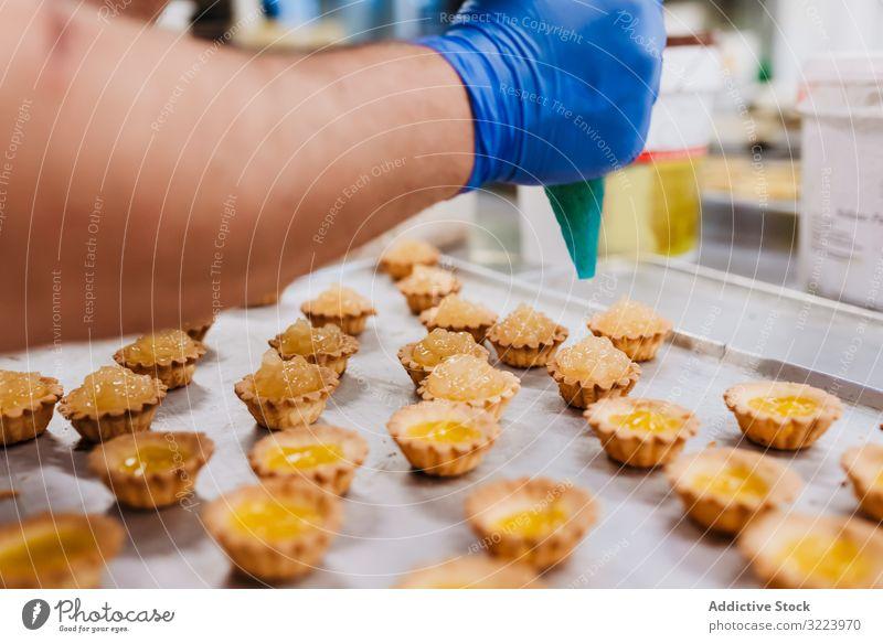 Erntebäcker, der Teig auf einem Blech auspresst Konditor Bäckerei Teigwaren drücken Tablett Keks Arbeit Küche Vorbereitung professionell Lebensmittel Papier