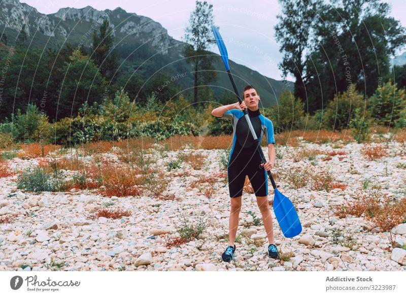 Weiblich stehend mit Paddel am Ufer Frau Training Sport Sella Fluss Spanien Kajakfahren üben Aktivität Lifestyle ernst konzentriert sportlich passen jung