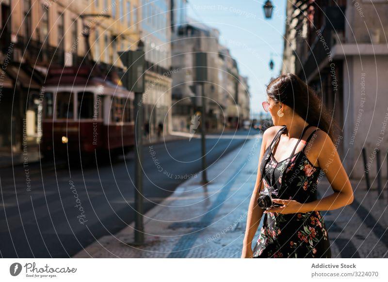 Frau, die eine Kamera hält, während sie auf der Straße steht Stadt reisen lässig Fotokamera selbstbewusst Bild malerisch Lissabon Portugal sonnig Großstadt
