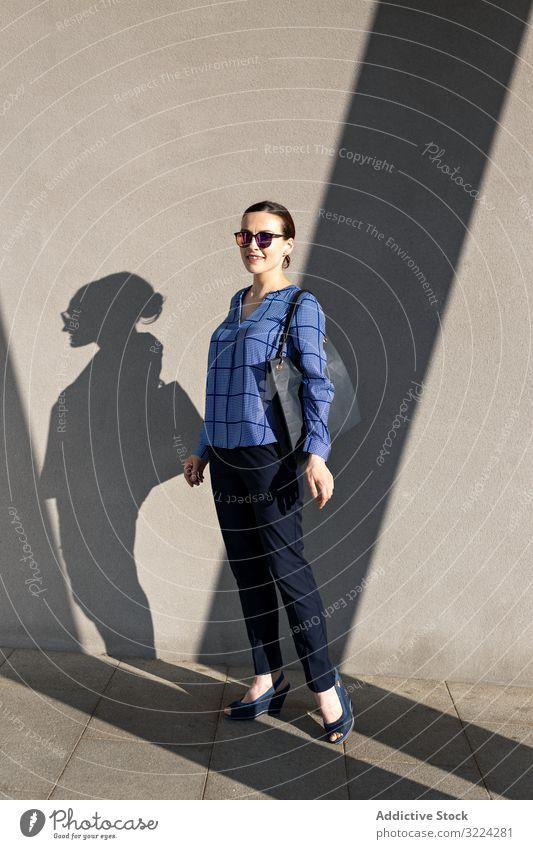 Lächelnde Geschäftsfrau steht an grauer Wand Straße Großstadt Gebäude Straßenbelag elegant modern urban Frau Manager Unternehmer Karriere Tasche Sonnenbrille