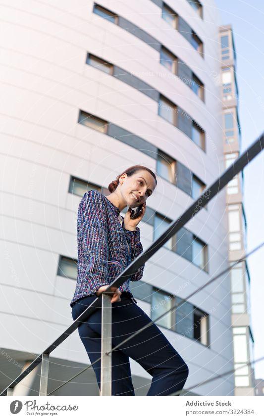 Lächelnde Geschäftsfrau nimmt Telefonanruf entgegen Smartphone Straße reden Gebäude modern Großstadt urban Frau Mitteilung Arbeit Job Mobile Gerät Apparatur