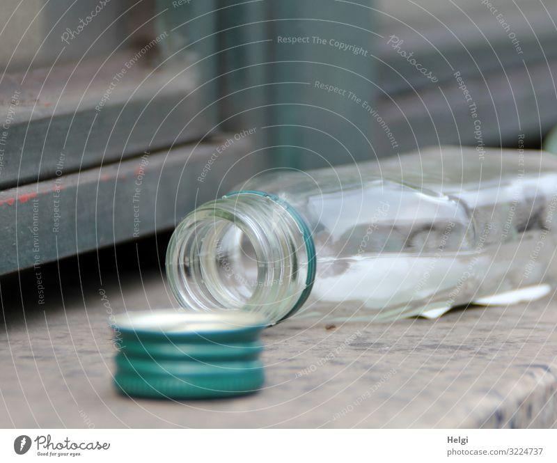 leere geöffnete Alkoholflasche liegt auf einer Mauer Wand Flasche Verschluss Verschlussdeckel liegen authentisch klein grau grün Gefühle Verzweiflung