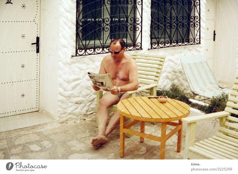 Zwischenlektüre Häusliches Leben Wohnung Stuhl Tisch Bildung lernen maskulin Mann Erwachsene 1 Mensch Terrasse Fenster Tür Hose Sonnenbrille brünett kurzhaarig