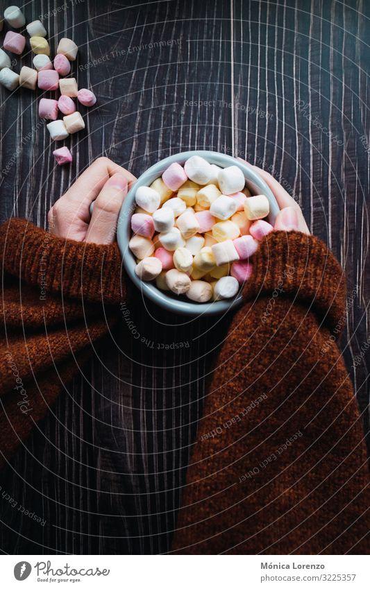 Frau hält eine Tasse heiße Schokolade mit Marshmallows in der Hand. Dessert Winter Dekoration & Verzierung Erwachsene Pullover weich gelb rosa weiß Farbe Zucker
