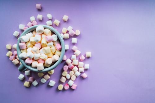 Heiße Schokolade mit bunten Marshmallows auf violettem Hintergrund. Dessert Getränk Winter Dekoration & Verzierung heiß weich gelb rosa weiß Farbe Zucker Tasse