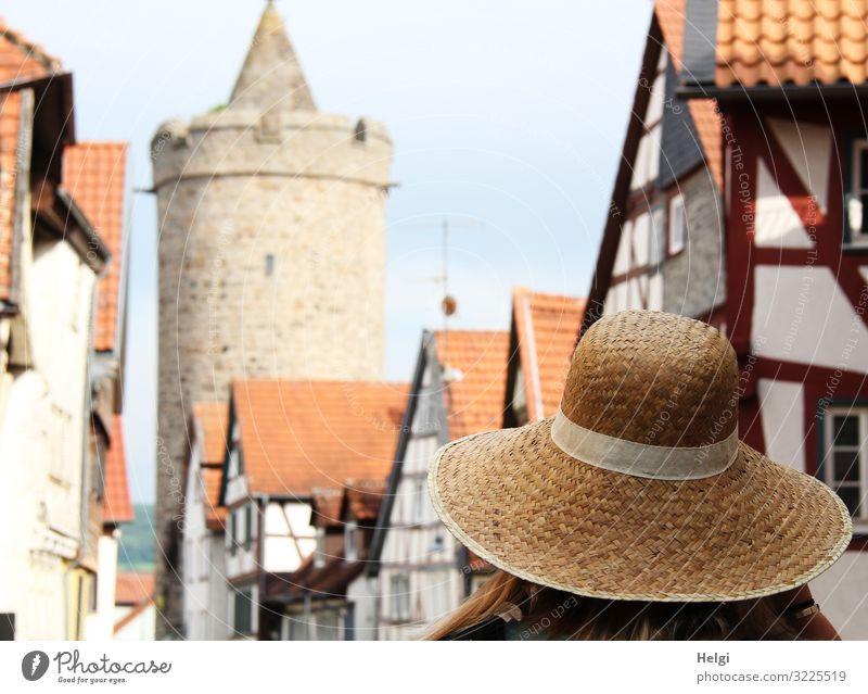 Dame mit Sonnenhut spaziert in einer Altstadt mit Fachwerkhäusern und historischem Turm Mensch Erwachsene 1 Alsfeld Stadt Haus Bauwerk Architektur Fachwerkhaus